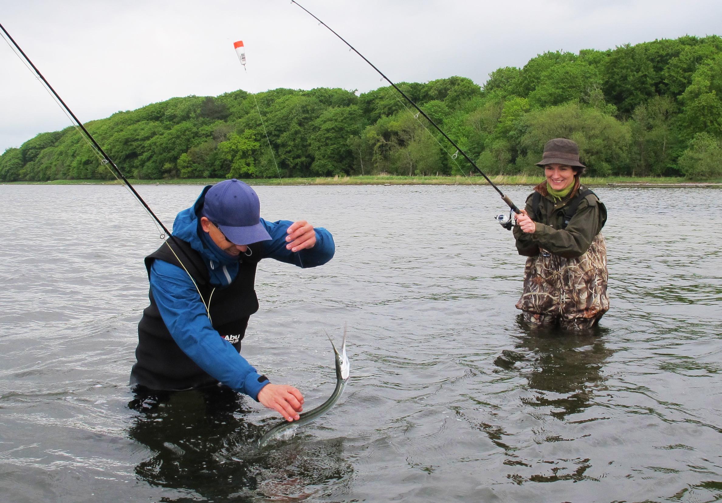 Fiskeguide Jonas Kærlin hjælper Grethe Saabye med at lande hendes først fisk nogensinde.